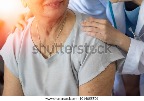 Geriatrische Ärztin oder Geriatrie-Konzept.  Ärztin gibt glückliche ältere Patientin auf, sich in einem Krankenhaus- oder Krankenhausaufenthalt zu wohlfühlen.