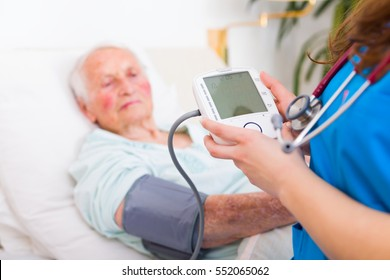 Geriatric doctor measuring senior woman's blood pressure - blank LCD display.