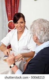 A geriatric nurse helping senior at breakfast