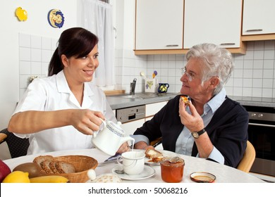 A geriatric nurse helping senior at breakfast