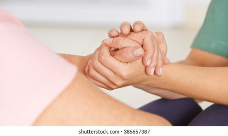 Geriatric nurse holding hands of senior woman for consolation