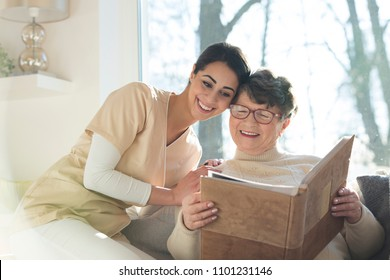 Geriatric patient with dementia together with a professional rehabilitation nurse looking at a family photo album in a private assisted living home