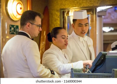 Gerinanger, Norway - august 6, 2018: Selective focus image of a group of waiters checking data on a restaurant computer from a Norwegian fjord cruise