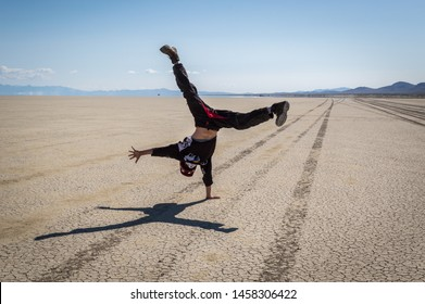 Gerlach, Nevada / United States - July 04 2019: A young man does a cartwheel on the playa of the Black Rock Desert.