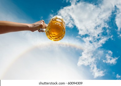 A german beer on a backdrop of blue sky and white clouds and authentic rainbow.