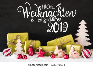 German Calligraphy Frohe Weihnachten Und Ein Glueckliches 2019 Means Merry Christmas And A Happy 2019. Green Christmas Decoration Like Tree, Balls Gifts And Reindeer. Cement Background With Snow