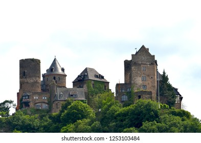 A German castle made of brown stones sits on top of a hill, surrounded by trees and bushes. The turrets and towers rise into a pale sky filled with white clouds.