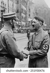 German Chancellor, Adolf Hitler, shaking hands with a Brownshirt at Nazi Party Day. Nuremberg, 1937. )