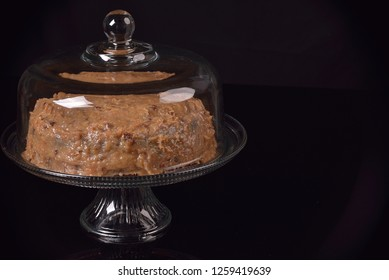 German Chocolate cake with in a crystal glass stand on a black pallet with room for text.