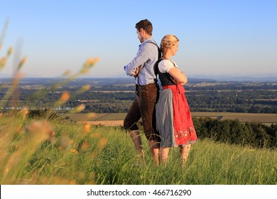 A German Couple in Bavarian Costume back to back on grass