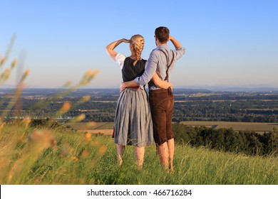 A German Couple in Bavarian Costume on the lookout in nature