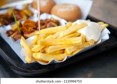 German Currywurst sausage with curry ketchup and French fries with mayonnaise on food market