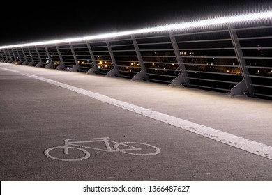 German cycle path illuminated at night by the railing of a bridge. The road is marked by the bicycle symbol.