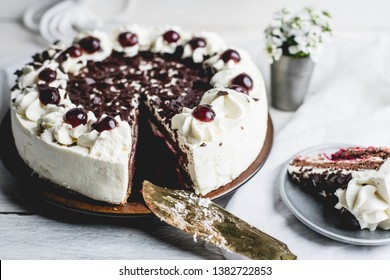 German, delicious Black Forest cake, with a delicate white cream, cherries in alcohol and dark chocolate on a white wooden background decorated with white linen fabric and white flowers