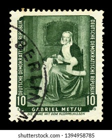 """German Democratic Republic (East Germany) - circa 1959: A stamp printed in G D R shows """"The Needlewoman"""" (Lacemaker) by Gabriel Metsu, series returned paintings from the Dresden gallery, circa 1959"""