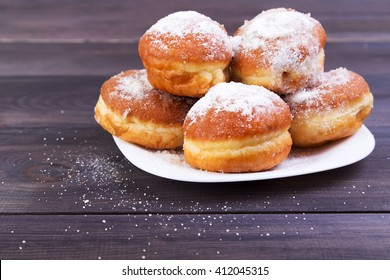 German donuts - berliner with icing sugar on plate on a dark wooden background