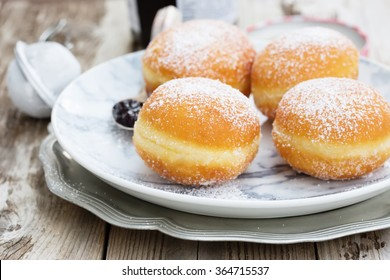 German donuts - krapfen or berliner - filled with jam. On wooden table. Selective focus, natural light.