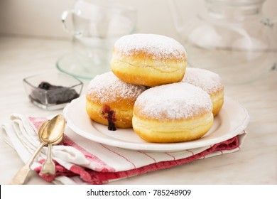 German donuts - krapfen or berliner - filled with jam. On white marbled table. Selective focus.