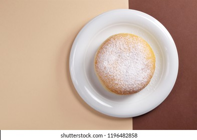 German doughnut berliner with powdered sugar in plate on a two-tone brown background, top view with copy space