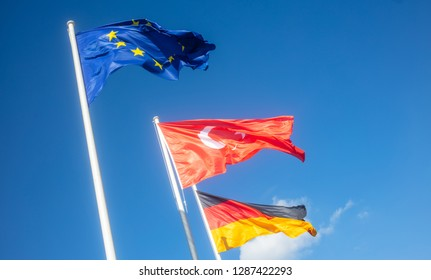 German, European Union, Turkey waving flags on white poles. Looking for friendship and co-operation. Blue sky background.