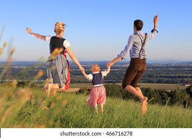 A German Family in Bavarian dress jumping happy meadow