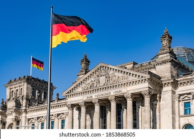 The German federal flag in front of the monumental Reichstag in Berlin as a symbol of the separation of powers