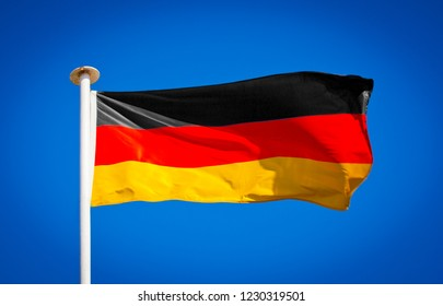 German flag blowing in strong wind against pure blue sky. Tricolour, symbol of national patriotism.