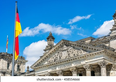 German flag next to the Reichstag. The Reichstag is a historical building situated in Berlin, Germany.