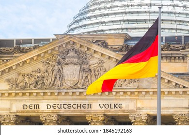 German flag on a background Reichstag building. The seat of the German Parliament or Bundestag, Berlin Mitte district. Inscription in German: To the German People