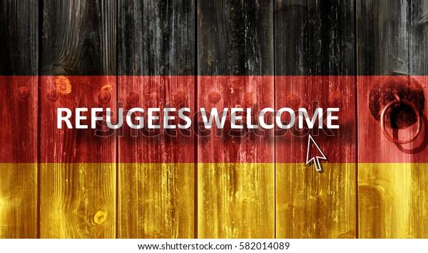 German flag painted on an old wooden door. Next to the door handle text Refugees Welcome