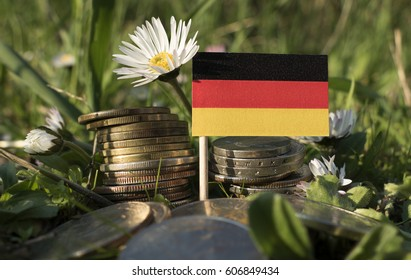 German flag with stack of money coins with grass and flowers