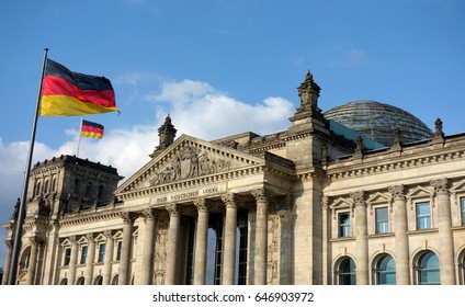 German flag waving at Bundestag building in Berlin Germany in a sunny day with blue sky.