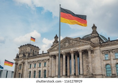 German flags waving in the wind at Reichstag building - seat of the german parliament (Deutscher Bundestag), Berlin, Germany