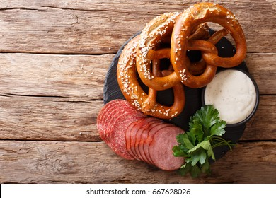 German food: sliced sausages and pretzels with cream sauce close-up on the table. horizontal view from above