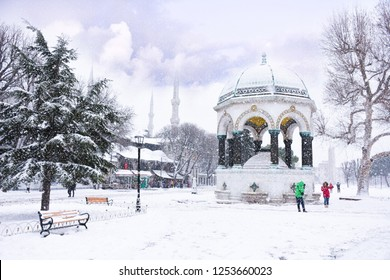 German Fountain in old Hippodrome, Istanbul, Turkey in winter day with snow, one tourist group walk around.