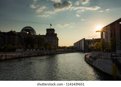 German governmental Reichstag during sunset with the sun looking like a star just on top of a building with the river Spree flowing through the city of Berlin