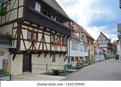 German half timbered building in medieval town next to small canal in the Swabian Jura region