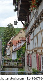 German half timbered building in medieval town built alongside a small canal, in the Swabian Jura region. A watering can provides water for the window boxes