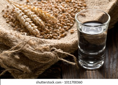 German hard liquor Korn Schnapps in shot glass with wheat grains and ears on burlap sack on rustic wooden table