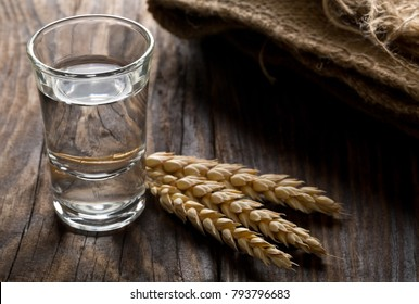 German hard liquor Korn Schnapps in shot glass with wheat ears on rustic wooden table