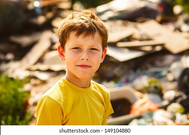 German homeless boy child is on a garbage dump in a yellow T-shirt