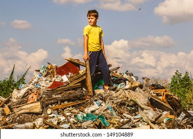 German homeless boy child is on garbage dump in yellow T-shirt