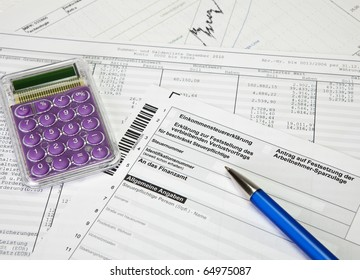 German income tax return form with calculator, charts and ballpoint pen