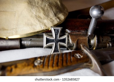 A German Iron Cross award for valor stands with a gun and bayonet from World War I. The traditional spiked helmet rests on top of the bolt-action Mauser rifle.