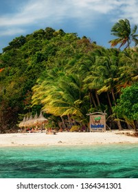 German island, San Vicente, Philippines - February 4, 2019: Sandy beach with turquoise water and green palm trees on tropical island