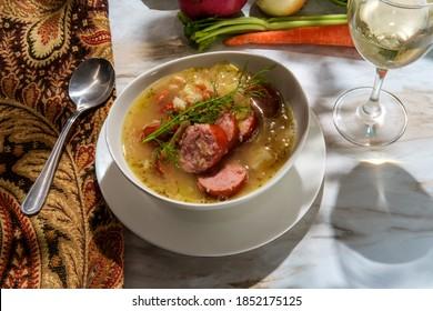 German kielbasa Oktoberfest stew with cabbage potatoes and a glass of white wine