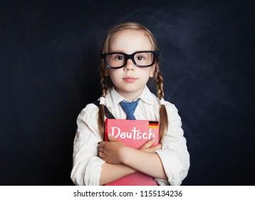 German language concept. Cute kid schoolgirl in classroom against chalkboard background