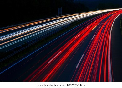 "German Motorway called ""Sauerlandlinie"" with six curved lanes at blue hour after sunset near Hagen Westphalia with colorful light traces of passing cars and trucks"