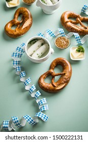 German Munich Weißwurst white sausage in porcelain pot, Bavarian sweet mustard, butter and pretzel with Oktoberfest streamers on pastel green background
