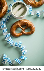German Munich Weißwurst white sausage in porcelain pot and pretzel with Oktoberfest streamers on pastel green background